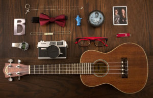 A ukelele, camera, bow tie, and glasses.