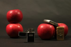 A still life of apples and lighters.